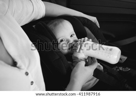 Black and white portrait of mother feeding baby from bottle in car - stock photo