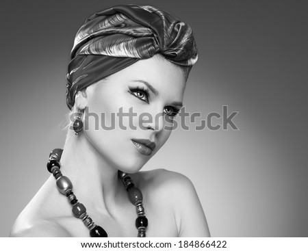 Black and white portrait of pretty woman in turban wearing jewelery. Young beautiful Caucasian female model with professional makeup posing in studio.