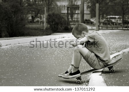 Black and white portrait of sad lonely child who sitting on skateboard in  park - stock photo