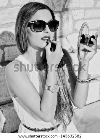black and white portrait of seductive blond woman sitting against a wall and doing make up . vintage and retro fashion style. - stock photo