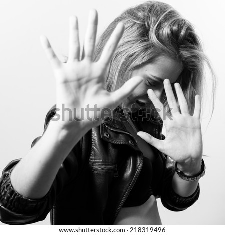 black and white portrait of sexy blonde girl in black leather jacket hiding face from camera on light copy space background - stock photo