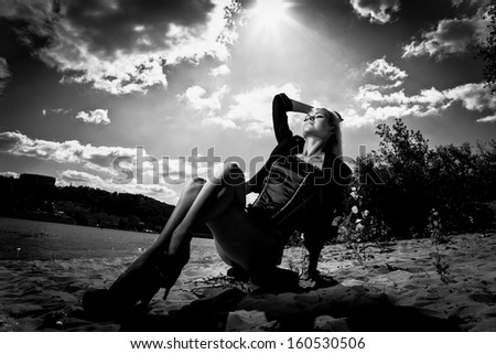 Black and white portrait of sexy blonde girl sitting on beach against sun - stock photo