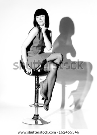 Black and white portrait of sexy woman in dress and stockings sitting on chair