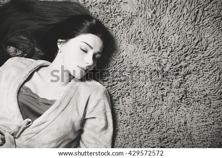 Black and white portrait of sleeping beautiful young female having fun relaxing on carpet copy space background