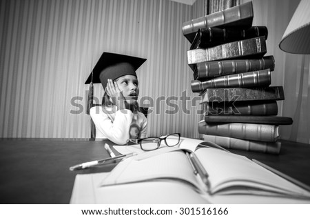 Black and white portrait of smart girl in graduation cap looking at high heap of books - stock photo