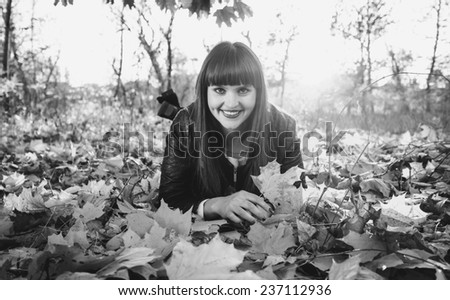 Black and white portrait of smiling woman lying on leaves at autumn forest - stock photo