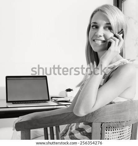 Black and white portrait of student woman at her home desk, using smartphone to have a conversation, and a laptop computer to work and study. Professional woman with mobile phone indoors, smiling.