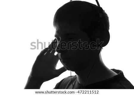 black and white portrait of the silhouette of a young man who enjoys listening to music on headphones