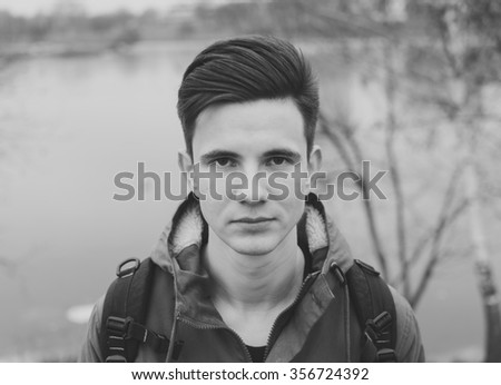 Black and white portrait of the young man on the city river - stock photo