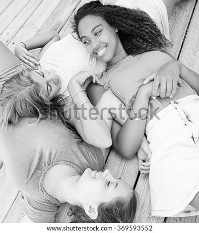 Black and white portrait of three ethnically diverse adolescent girls friends laying together on a wooden deck by the beach, smiling joyfully, relaxing outdoors. Recreation lifestyle, teenagers. - stock photo