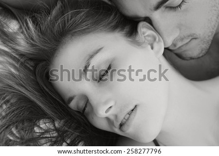 Black and white portrait of young attractive romantic couple hugging and kissing, laying down on a bed, having sex and being loving with each other. Love and relationships lifestyle, interior bedroom. - stock photo