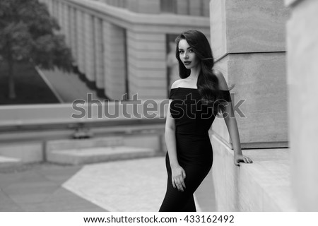 Black and white portrait of young beautiful elegant woman in black dress. Pretty sensual girl with long curly hair posing outdoors at city street - stock photo