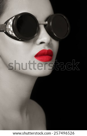 Black and white portrait of young beautiful girl in vintage steampunk glasses - stock photo