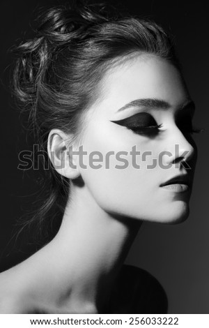 Black and white portrait of young beautiful girl with stylish cat eye makeup - stock photo
