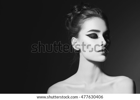 Black and white portrait of young beautiful girl with stylish winged eye make-up
