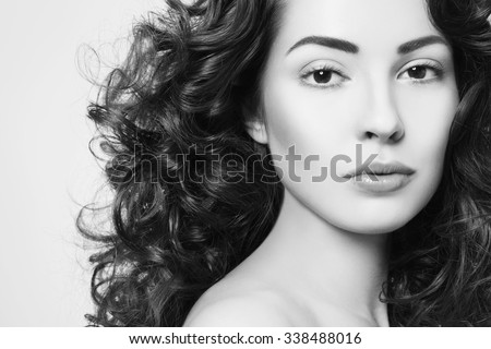Black and white portrait of young beautiful woman with long curly hair - stock photo
