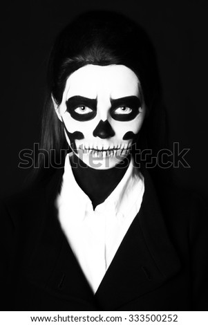 Black and white portrait of young beautiful woman with skeleton face art makeup, looking at the camera, black background.