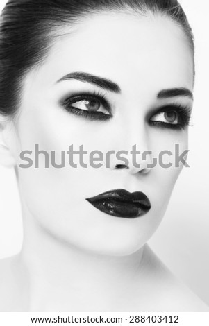 Black and white portrait of young beautiful woman with smoky eyes make-up - stock photo