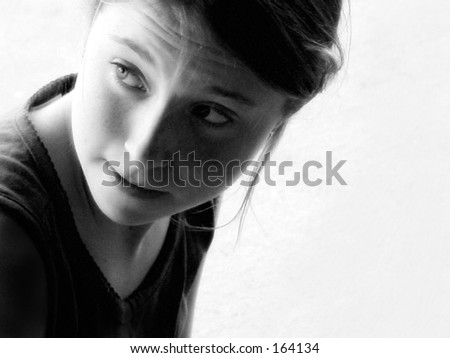 Black and white portrait of young girl looking over shoulder - stock photo