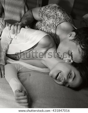 Black and white portrait of young lovers couple laying together hugging in bed home interior, hugs and affection, indoors. Relationships lifestyle, bedroom passion. Boyfriend and girlfriend closeness. - stock photo