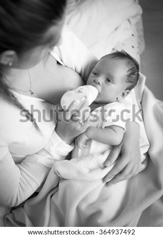 Black and white portrait of young mother feeding baby with milk from bottle