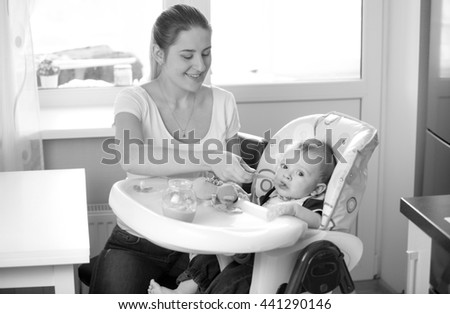 Black and white portrait of young smiling mother feeding her baby from spoon on kitchen - stock photo