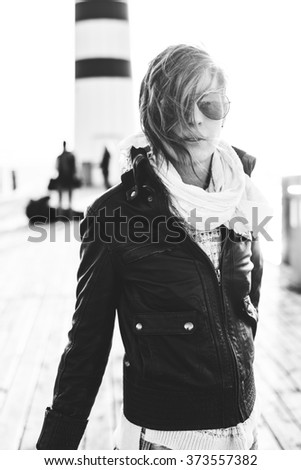 Black and white portrait photo of young woman posing outdoor in aviator style sunglasses, wind blowing - stock photo