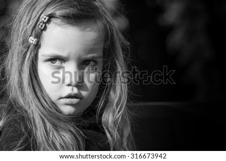 black and white portrait taken outside of a beautiful little girl with long hair, vintage look