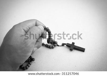 Black and white, prayer man hand with rosary - stock photo
