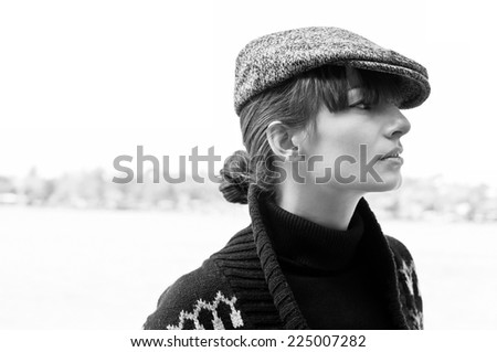 Black and white profile portrait of pretty stylish young woman outdoors wearing black turtle-neck, boyish peaked cap and sweater, looking aside. High key portrait, copy space - stock photo