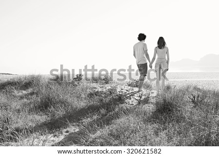 Black and white rear of a young tourist couple holding hands together in the distance on beach on holiday, contemplating outdoors. Travel and vacation lifestyle, nature living spacious exterior. - stock photo