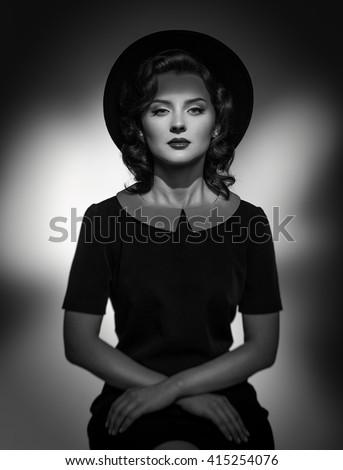 Black and white Retro classic portrait of elegant woman in hat and dress. Studio shot. - stock photo