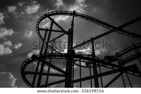black and white rollercoaster track in funny amusement park. - stock photo