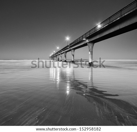 Black and White Seascape and Pier in New Brighton Beach, Christchurch, New Zealand.  - stock photo