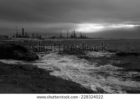 Black and white seascape at dusk seeing a big oil refinery in the background. Used infrared filter. - stock photo