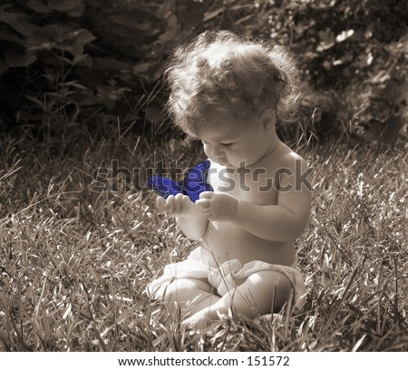 black and white sepia toned vintage look photo of baby outdoors playing with blue colored butterfly - stock photo