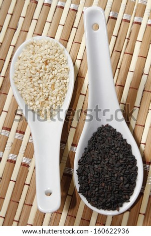 black and white sesame seeds on ceramic spoon