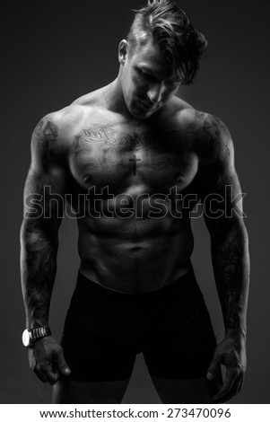 Black and white shoot of muscular man with tattooes. - stock photo