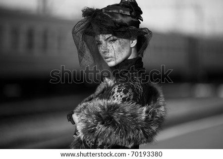 Black and white shoot of woman on train station; - stock photo