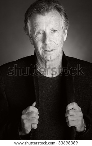 Black and White Shot of a Handsome Senior Man against Grey Background