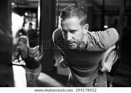 Black And White Shot Of Man Exercising With Gymnastic Rings - stock photo