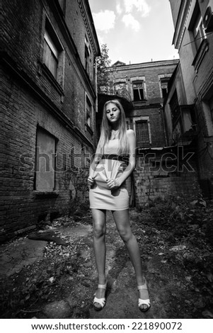 Black and white shot of woman standing against ruined building - stock photo
