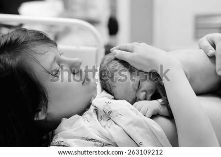 Black and white shot of young woman with newborn baby right after delivery - stock photo