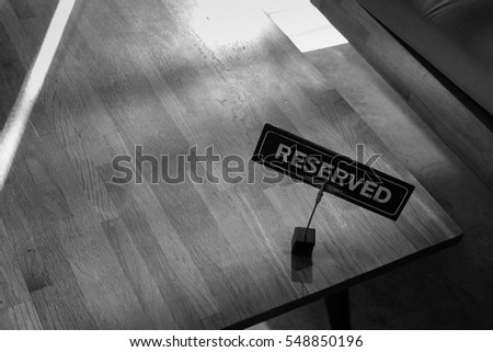 Black and white shot , Reserved sign under dark shadow put on table