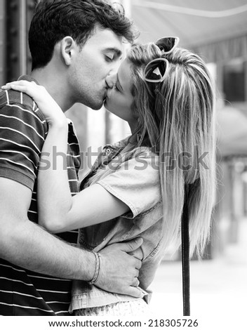 Black and white side portrait view of a young and attractive couple on holiday, kissing and embracing while shopping, traveling in a destination city street, outdoors. Love, passion and relationships. - stock photo