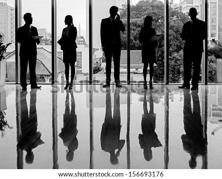 Black-and-white silhouettes of business people standing and working - stock photo