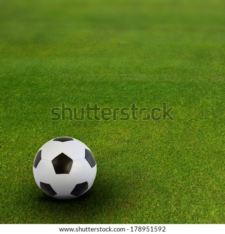 black and white soccer ball on green football field  background