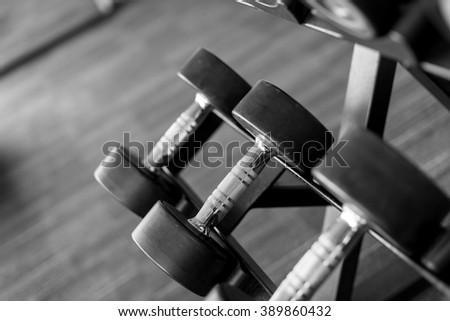 Black and white Sports dumbbells in modern sports club. Weight Training Equipment - stock photo
