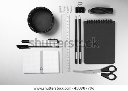 Black and white stationery on gray desk: notepads, pencils, scissors, stapler, clip, pins, ruler, pens, pen pot. Top view point. - stock photo