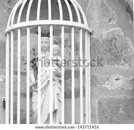 Black and white statue of mary and baby Jesus Christ in a protective cage. - stock photo